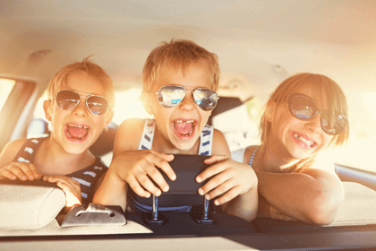 Kids laughing in the back seat of a car