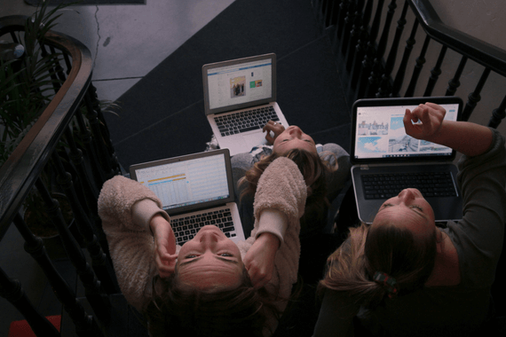 women using computers sitting on stairs