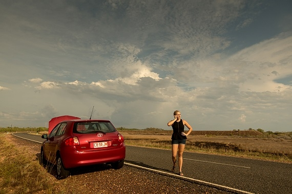 woman standing on the side of the road next to a broken down car